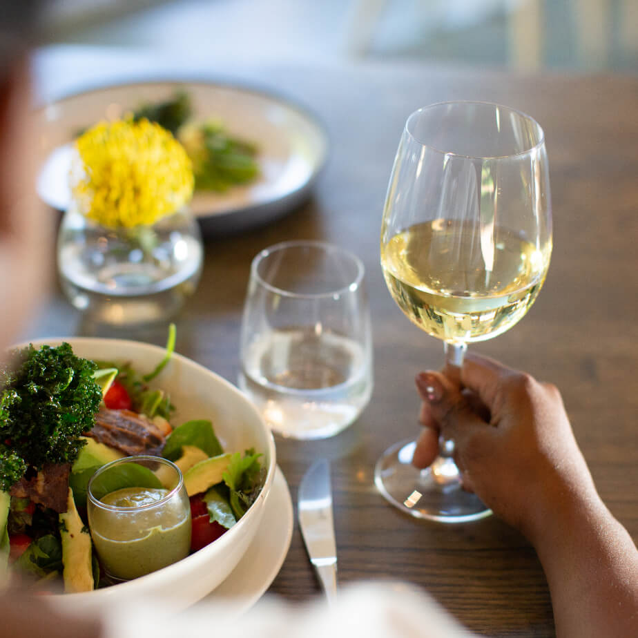 A glass of Vergelegen white wine being held by a customer with a salad bowl infront of them